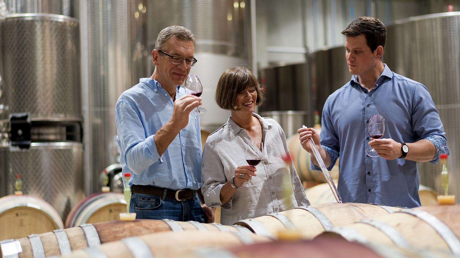 Ulrich, Ina und Christoph Kern probieren Wein aus einem Barriquefass
