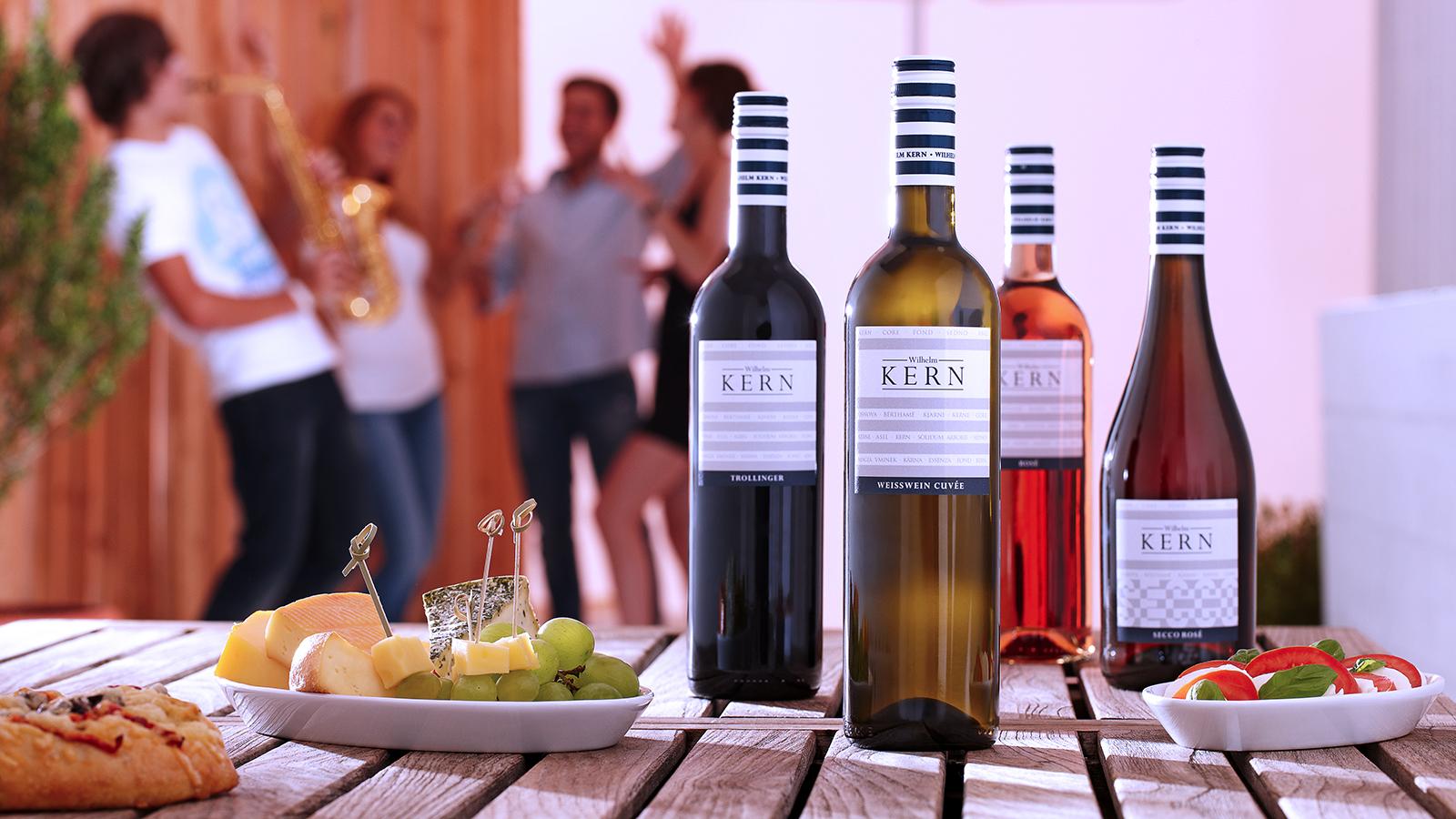 Flaschen der STREIF-Serie auf einem Tisch mit leichtes Esse, im Hintergrund feiernde junge Menschen